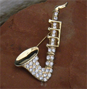 Vintage brooch of saxophone with gold metal and rhinestones.