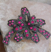 Festive vintage brooch of ribbon bow in textured metal covered with pink crystals