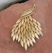 Vintage gold brooch is a spray of leaves.