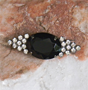 brooch has black glass faceted in oval shape decorated with rhinestones.