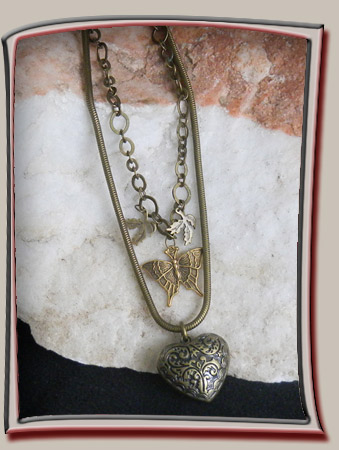 Designer necklace with Heart in bronze colored metal has deep texture