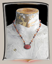 Necklace has coral-colored oval stone